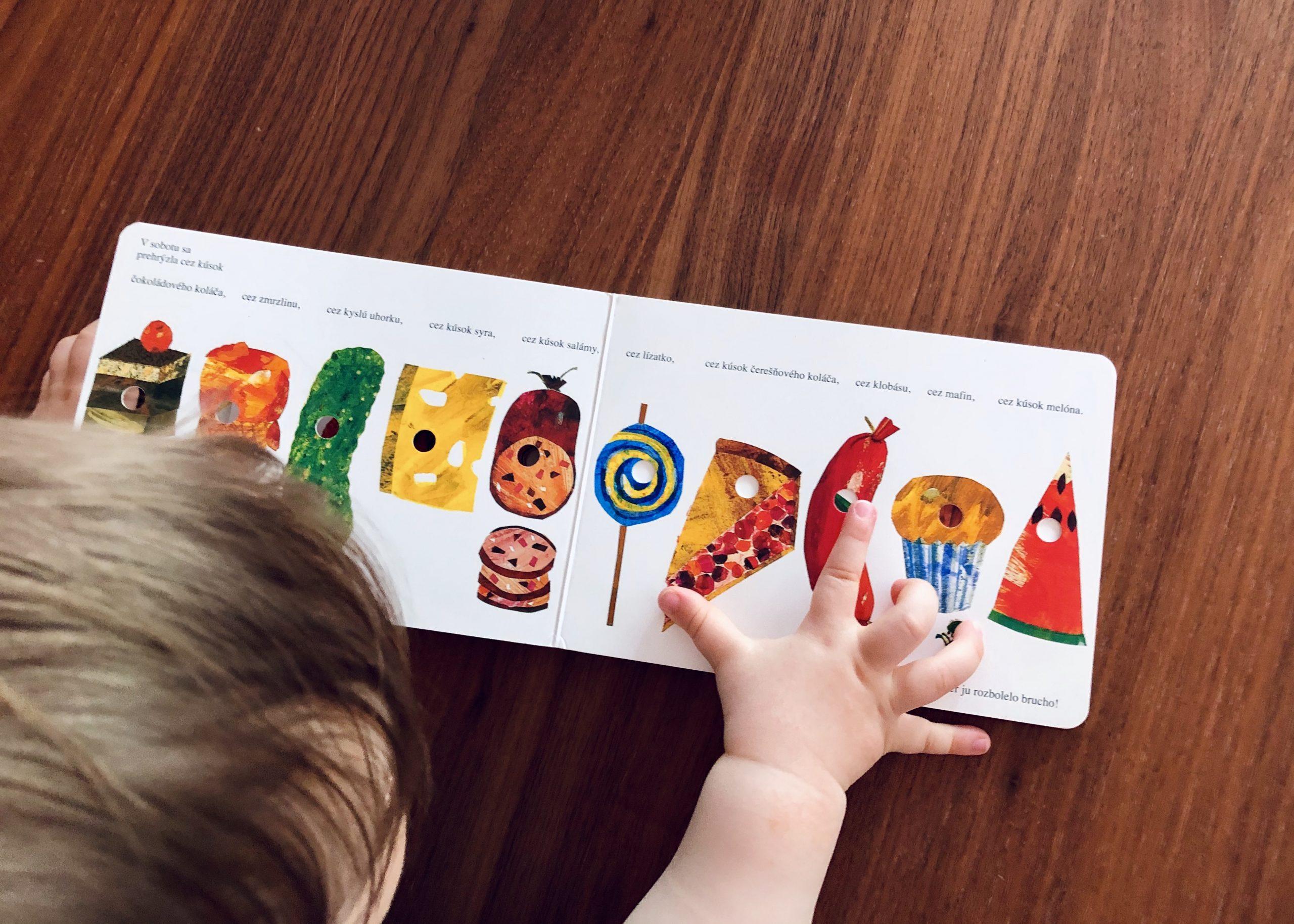 ročný chlapček číta leporelo